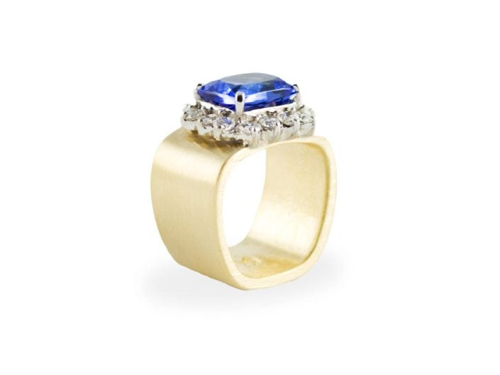 Sparkling 5ct violet blue, cushion-cut tanzanite in a 14k white gold setting atop a brushed 14k yellow gold square band. The bezel includes 14 round diamonds for a total of 1.2 ctw.