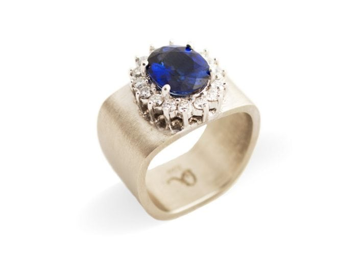 Stunning blue sapphire surrounded by 16 white diamonds atop a square 14k white gold band.