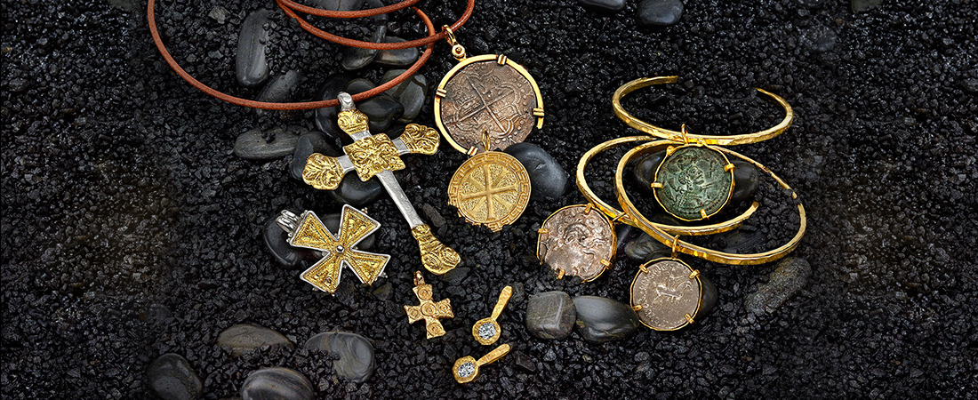 Variety of ancient coins, gemstones and artifacts set in 22k gold on leather cord necklaces.